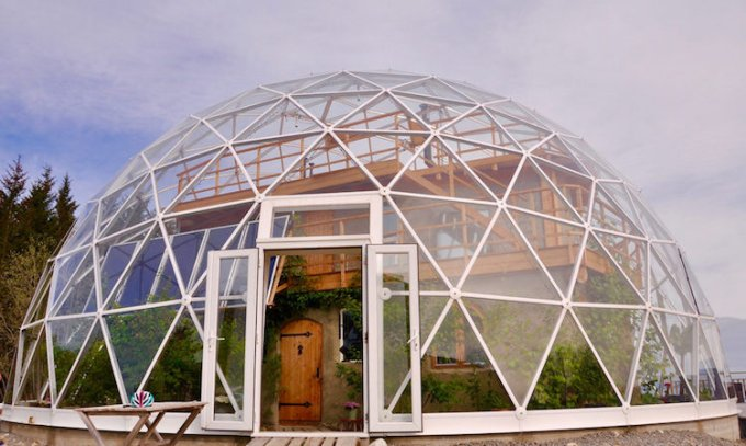 Cob house inside a greenhouse geodesic dome